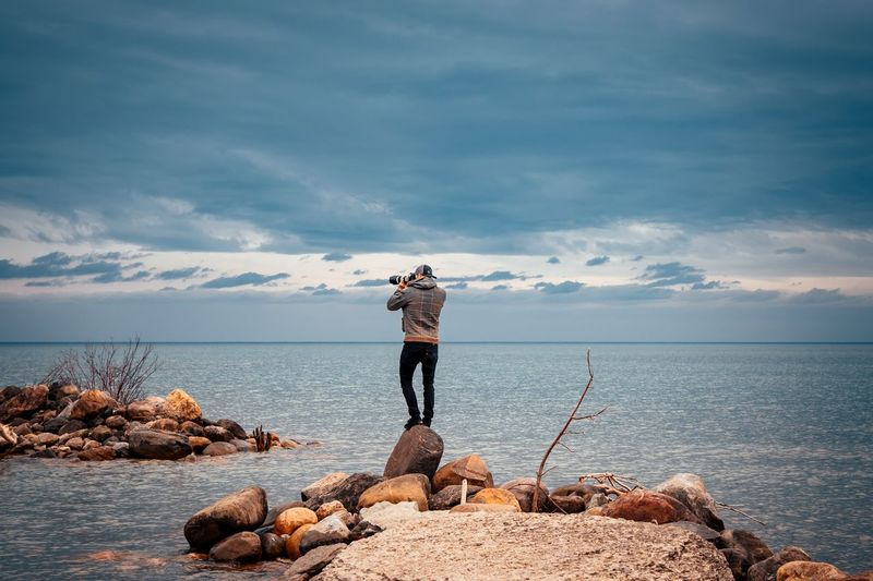 Rear view of man photographing sea while standing on rock against cloudy sky