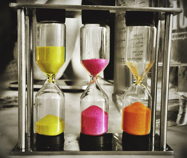 Close Up View Of Hourglasses With Multi Colored Sand