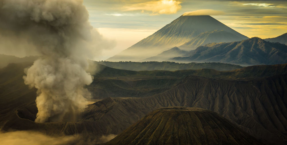 the mount Bromo and others volcanic craters are still active in Indonesia Beauty In Nature Erupting Geology Landscape Mountain Natural Disaster Nature No People Outdoors Power In Nature Scenics Sky Smoke - Physical Structure Sunset Toxic Tranquil Scene Volcanic Crater Volcano