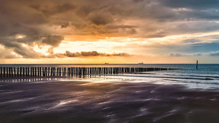 Sky Sea Cloud - Sky Water Sunset Scenics - Nature Beauty In Nature Horizon Over Water Beach Tranquility Land Tranquil Scene Horizon Nature No People Idyllic Orange Color Sand Dramatic Sky Outdoors Wooden Post