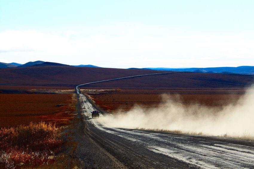 Dempster Highway Driving Beauty In Nature Car Dust Cloud Endlessness Landscape Mountain Mountain Range No People Outdoors Road Road Trip Scenics Tranquil Scene Winding Road