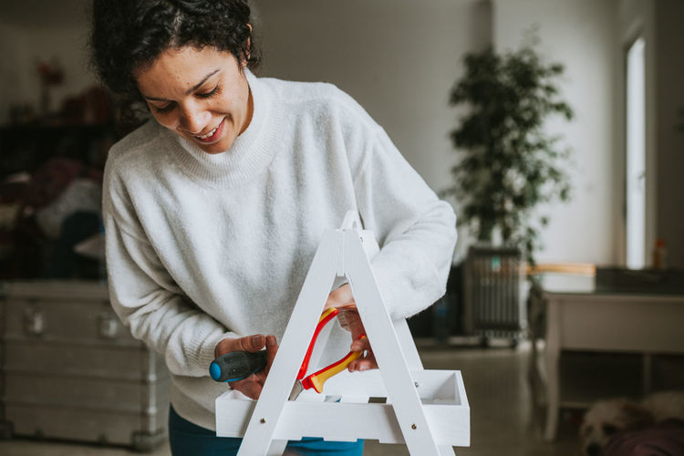 Motherhood Woman Lifestyles DIY DIY At Home House Handmade WoodLand Holding Standing One Person Indoors  Front View Looking Down Domestic Life Smiling Looking Casual Clothing Home Interior Hairstyle Happiness Young Adult Portrait Portrait Of A Woman International Women's Day 2019
