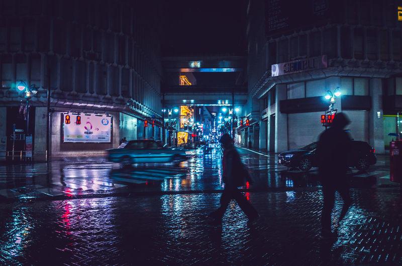 Silhouette People Walking On Wet Street In Illuminated City