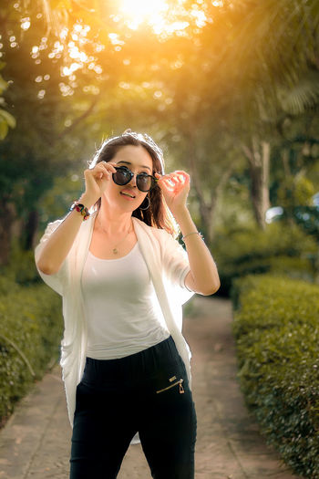 Backlit woman wearing sunglasses standing on pathway at park