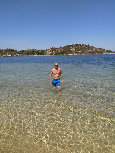 Full length of shirtless man in sea against clear sky