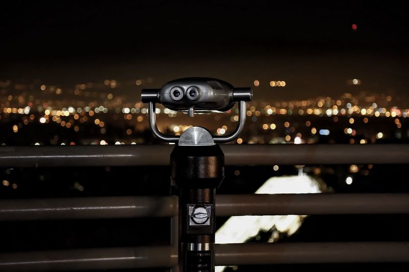 Coin-operated binoculars at observation point against cityscape at night