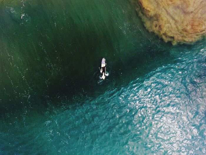 Directly Above View Of Person Lying On Surfboard In Sea
