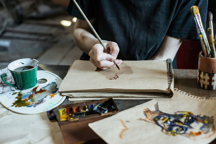 Art And Craft One Person Craft Real People Occupation Creativity Table Indoors  Working Skill  Workshop Human Hand Holding Making Work Tool Craftsperson Midsection Workbench Selective Focus Design Professional Art Arts Culture And Entertainment ArtWork Art And Craft Artistic Paintings Painting