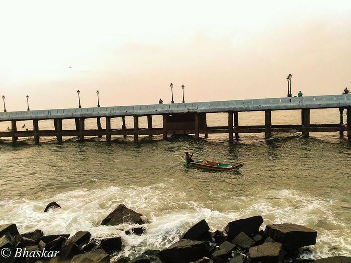 Fisherman returns from catch Beauty In Nature Bridge - Man Made Structure City Day Fisherfolk Fisherman Fisherman Boat Gondola - Traditional Boat Nature Outdoors Pier Sea Sky Sun Sunset Vacations Water