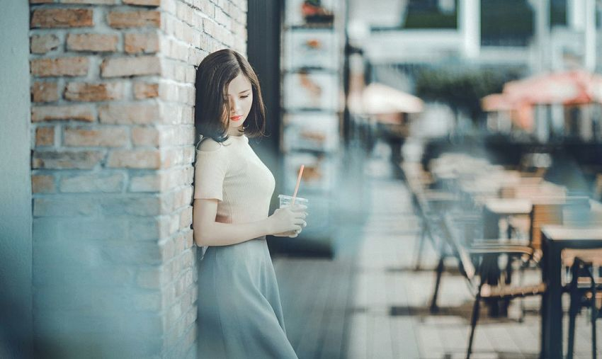 Side view of young woman holding coffee cup while standing by brick wall in city