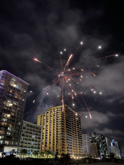 Low angle view of firework display in sky at night