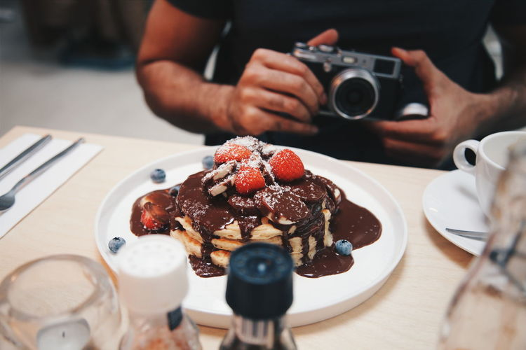 Pancake stack. Chocolate and berries. Food And Drink Food Freshness Sweet Food Real People One Person Dessert Photography Themes Indoors  Ready-to-eat Berry Fruit Indulgence Technology Plate Holding Camera - Photographic Equipment Temptation Hand Breakfast Breakfast ♥ Breakfast Time Chocolate Sauce Berries Pancakes Desserts
