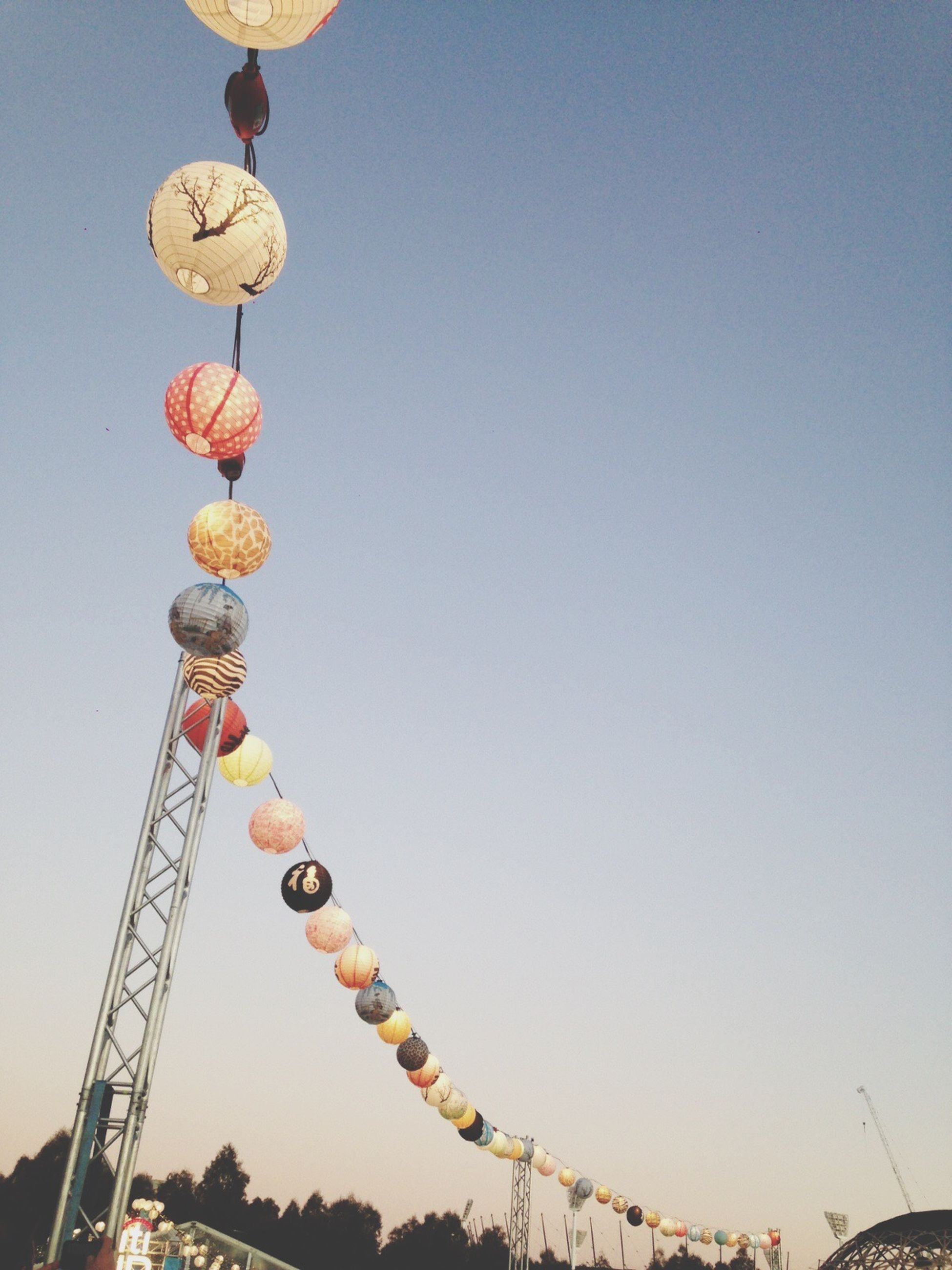 low angle view, clear sky, copy space, lighting equipment, street light, built structure, amusement park, blue, sky, hanging, architecture, amusement park ride, outdoors, decoration, in a row, no people, multi colored, lantern, day, arts culture and entertainment