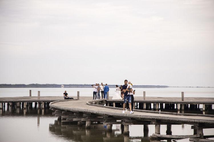People on pier over sea against sky