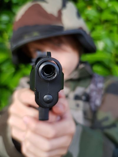 Close-up of army soldier aiming with gun