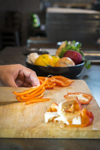 Cropped Hands Of Man Chopping Red Bell Pepper On Cutting Board