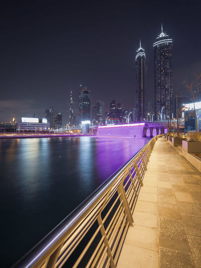 View of illuminated buildings by river at night