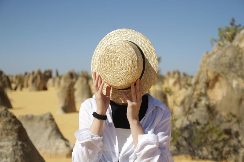 Woman covering face with hat against sky
