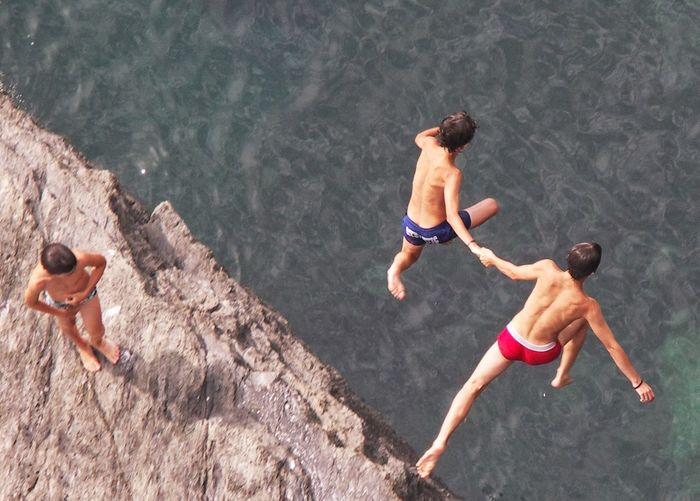 High angle view of shirtless man jumping in water