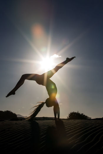 Woman in handstand on beach Woman Silhouette Beach Handstand  Upside Down Sunlight Shore Dynamic Asana Peace Balance Grace Healthy Eating Practice Harmony Position Outdoors Nature Training Lifestyles Energy Posture Freedom Sea Bright