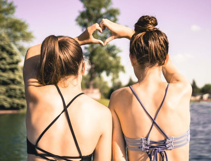 Rear view of friends making heart shape with hands against lake