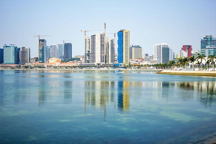 City skyline by sea against clear sky