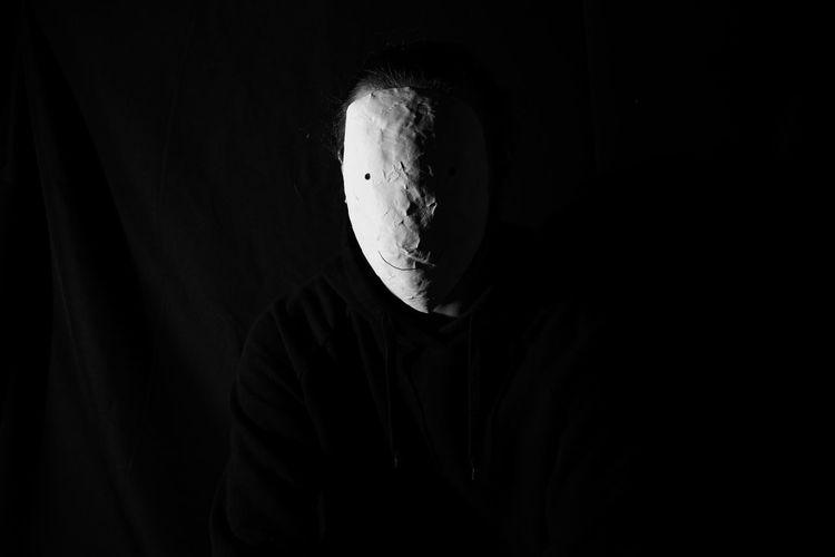 Portrait of man against black background wearing mask