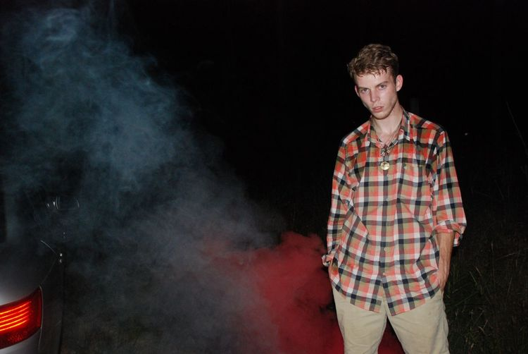 Young man standing by smoke on field at night