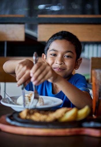 Portrait of boy having ice cream in restaurant