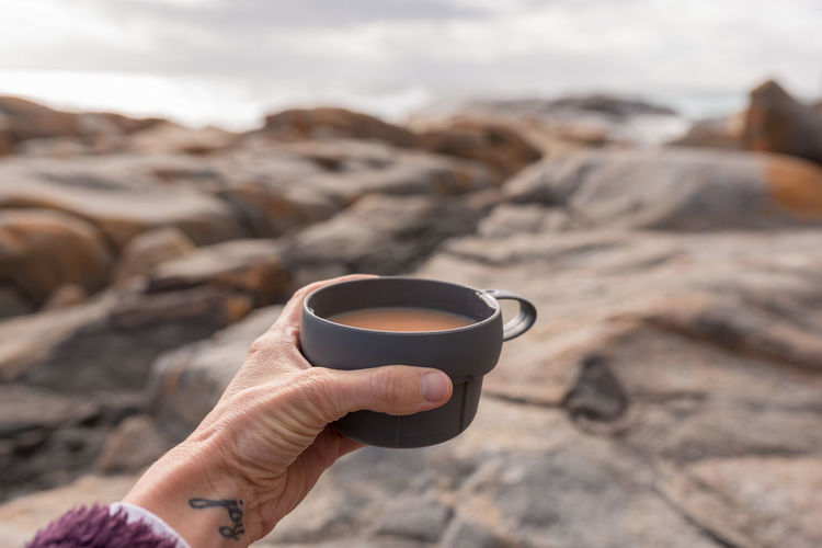 Woman's hand holding cup of tea against rocky beach outlook Body Part Coffee Cup Cup Day Drink Finger Focus On Foreground Food And Drink Hand Holding Hot Drink Human Body Part Human Hand Leisure Activity Lifestyles Mug Nature One Person Outdoors Real People Rock Tea Cup
