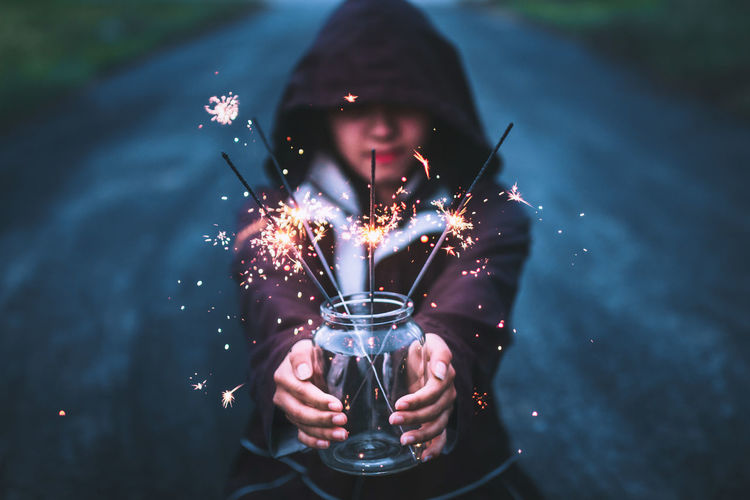 Young Woman Holding Sparklers In Jar On Road