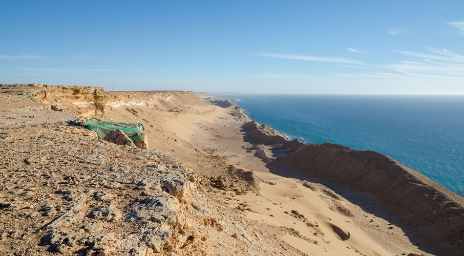 Scenic view of atlantic coast against blue sky with simple fisherman tent, western sahara, north africa