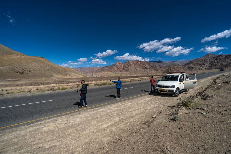 People on road by desert against sky