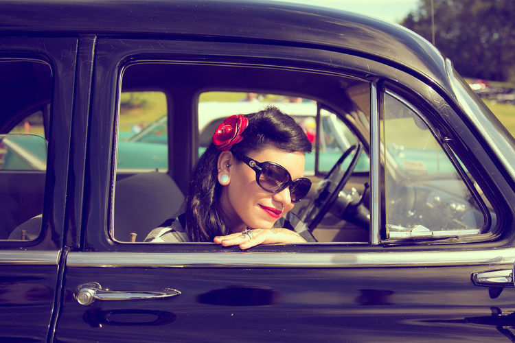 Portrait of smiling beautiful woman sitting in car