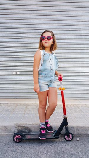 Full Length Of Girl Wearing Sunglasses Standing On Push Scooter In City