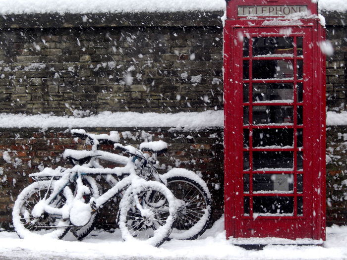 Bicycle parked on snow covered city in winter