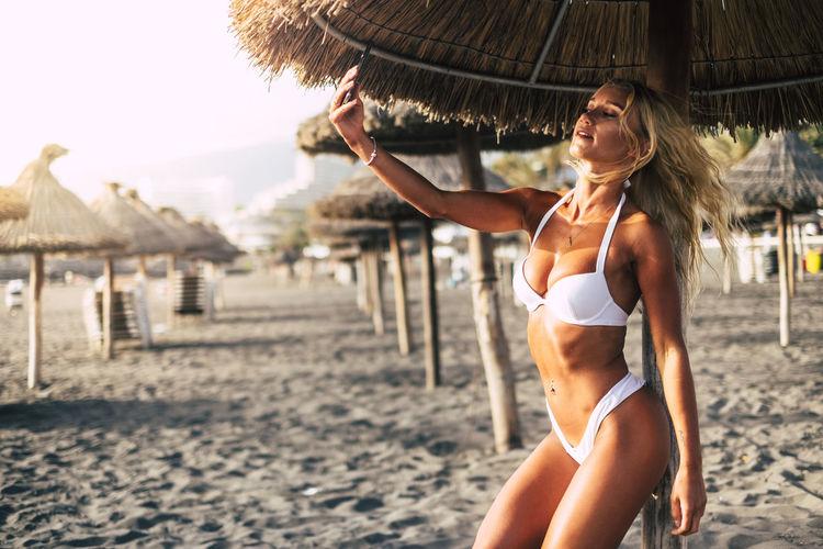 Young woman in bikini standing at beach