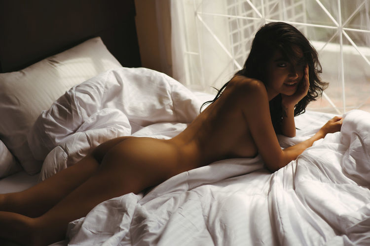Side View Portrait Of Sensuous Naked Female Model Lying On Bed
