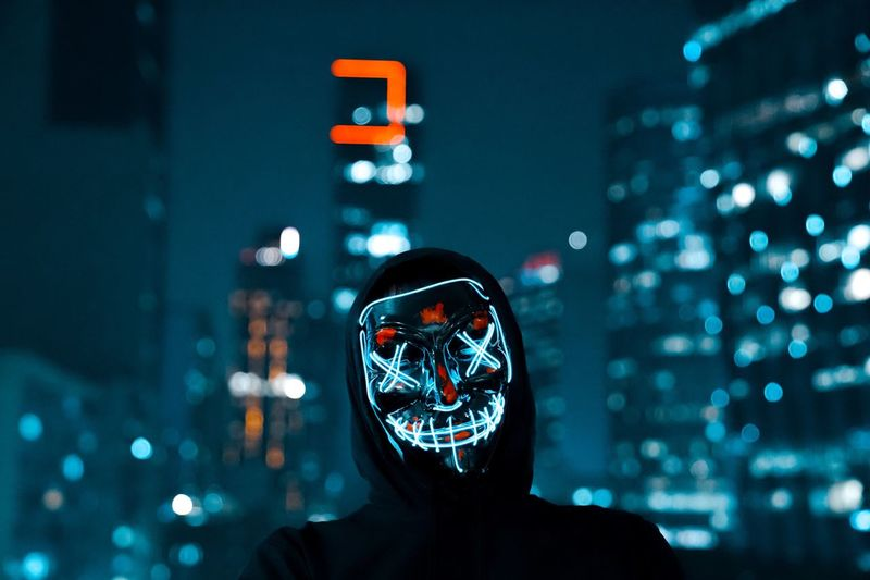 Man wearing illuminated mask in city at night