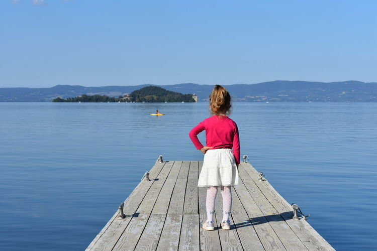 Rear View Of Girl With Hand On Hip Standing On Pier Against Sky