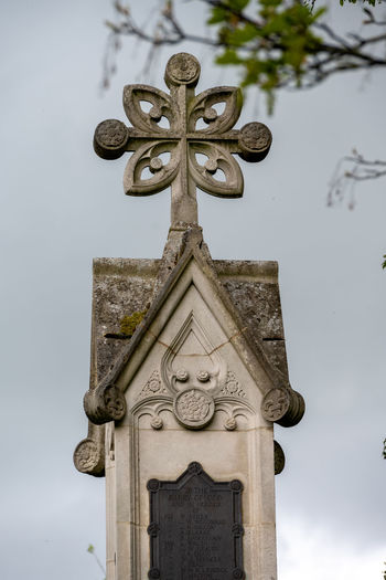 Low angle view of cross sculpture against sky