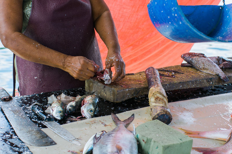 Midsection Of Woman Cleaning Fish On Cutting Board In Market