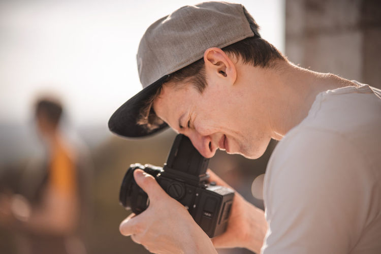 Portrait of young man holding camera