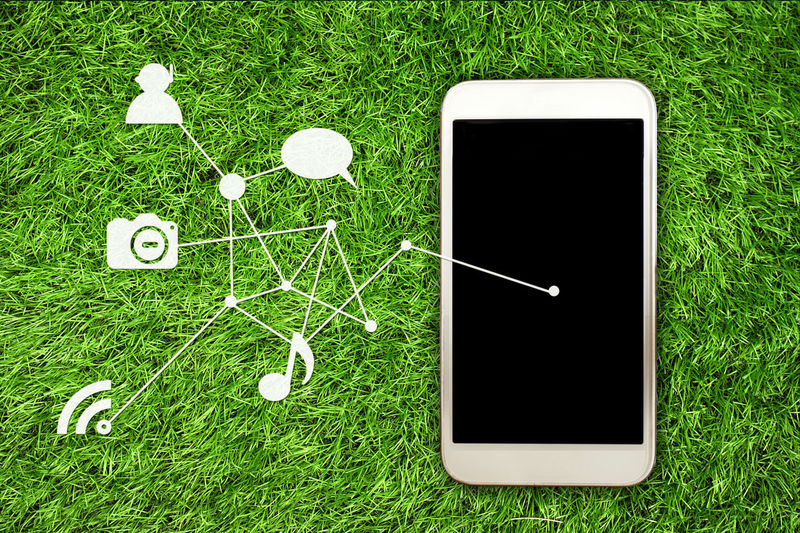 Directly above shot of smart phone and symbols on grass