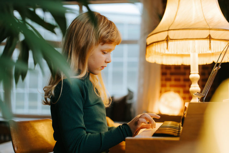 Young girl playing keyboard at home