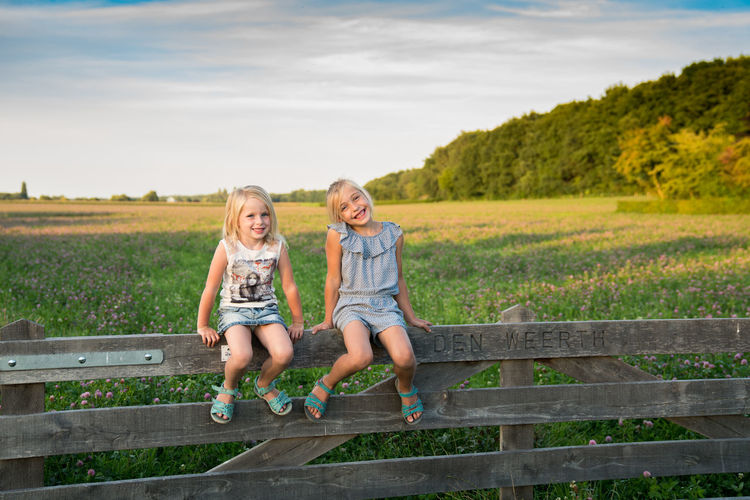 Blond Hair Bonding Casual Clothing Child Childhood Day Elementary Age Fence Field Front View Girls Happiness Leisure Activity Looking At Camera Nature Oudside Outdoors Portrait Real People Sitting Sky Smiling Togetherness Two People
