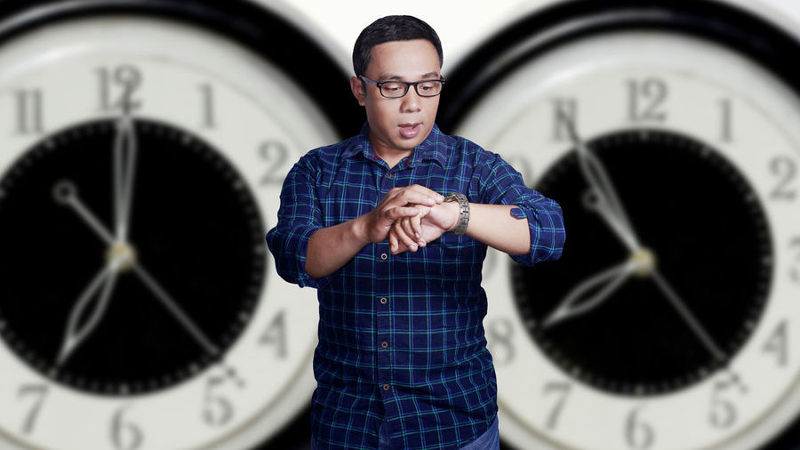 Portrait of a asian young man late for work concept with clock background Work Clock Eyeglasses  Hour Hand Late Lifestyles One Person Real People Standing Time Wristwatch