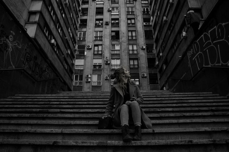 Low angle view of woman sitting on staircase of building