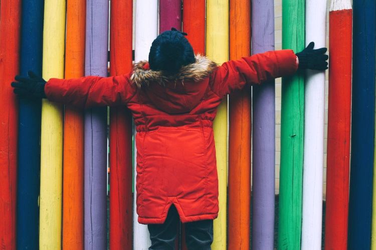 Trying to blend in | Real People Multi Colored Jacket One Person Full Length Arms Outstretched Leisure Activity Outdoors Standing Built Structure Colors Red People People Watching Woolly Hat Cold Winter EyeEm Gallery Taking Photos Eye4photography  Exploring