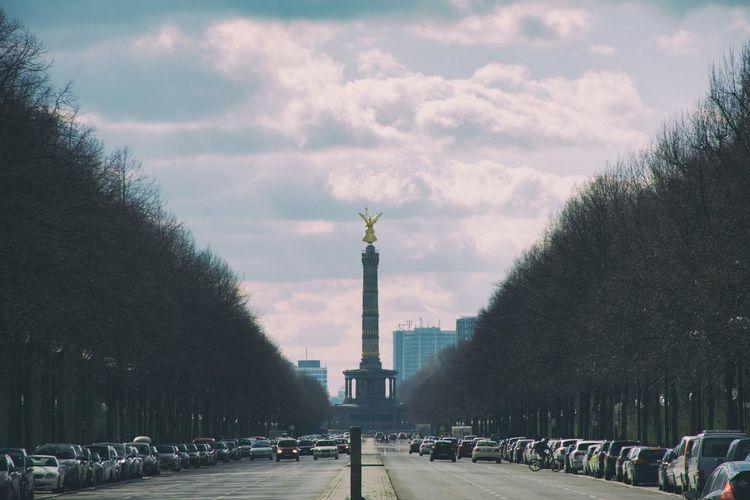 Road leading towards berlin victory column in city against sky